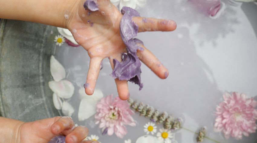 Child's wet hands with squishy soap over a tub of water with filled with flowers and petals, taken from The Joy Journal for Magical Everyday Play by Laura Brand