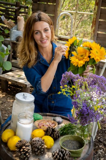 Laura Brand holding a bunch of sunflowers by an outdoor mud kitchen with a tray of natural materials including lemons, soil and pine cones, for The Joy Journal for Magical Everyday Play by Laura Brand