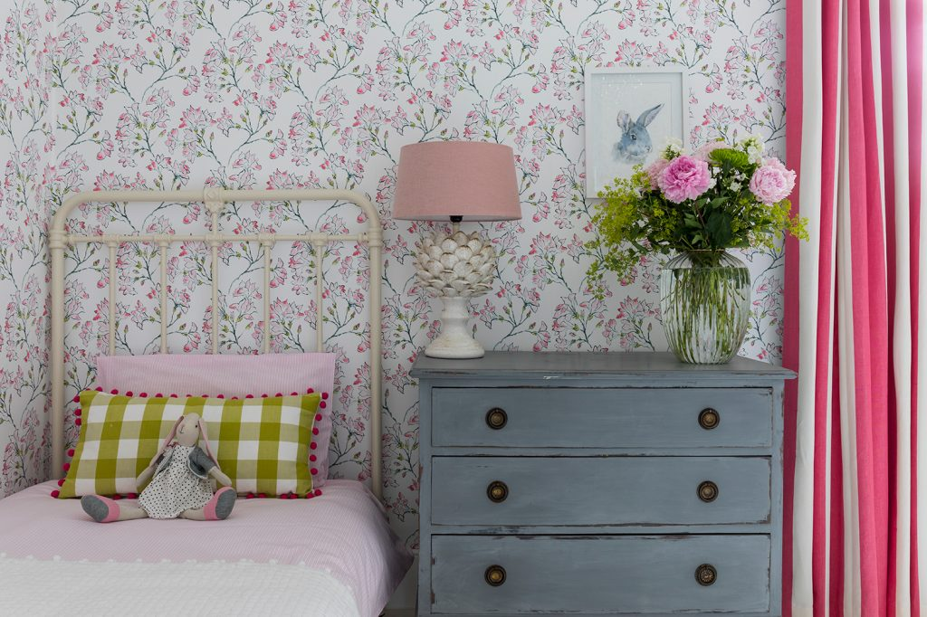 Laura Stephens girl's bedroom antique chest of drawers iron bed wallpaper © Chris Snook