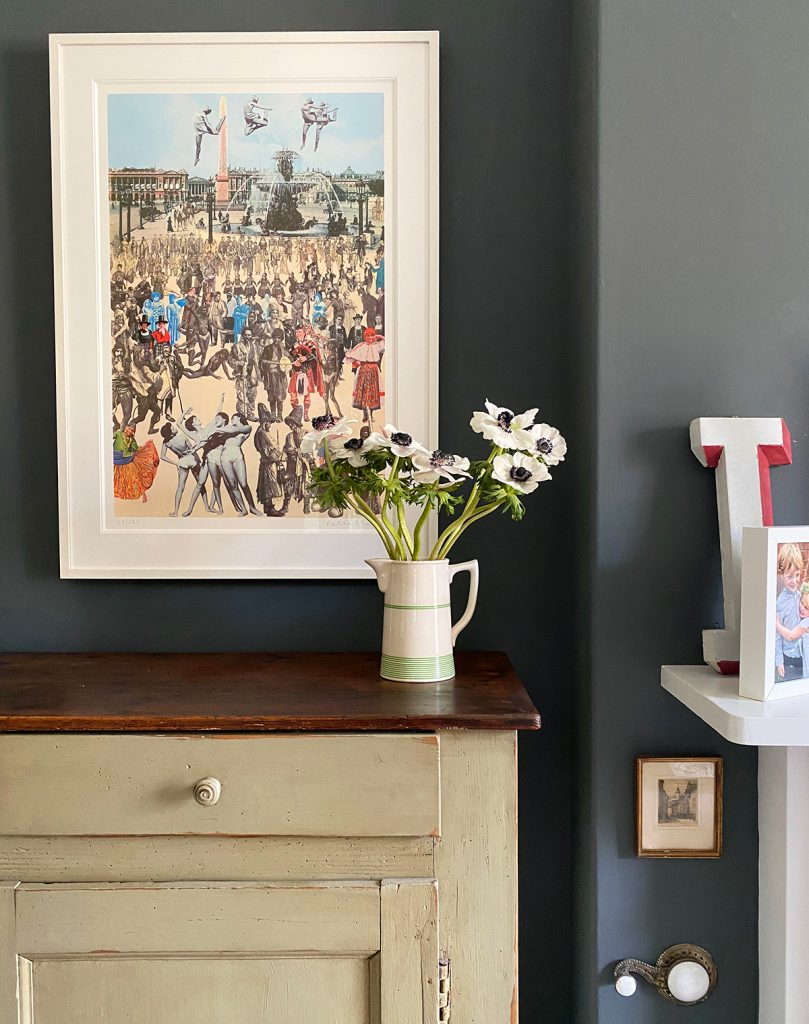 Framed Peter Blake collage hanging above vintage chest, vintage jug with fresh flowers at the home of Natalie Williams, founders of Medium Room