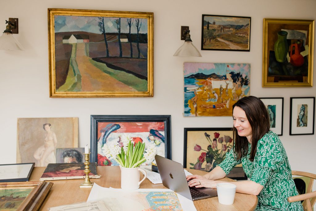 Natalie Williams founder of Medium Room on her laptop at the dining room table with gallery wall of vintage art