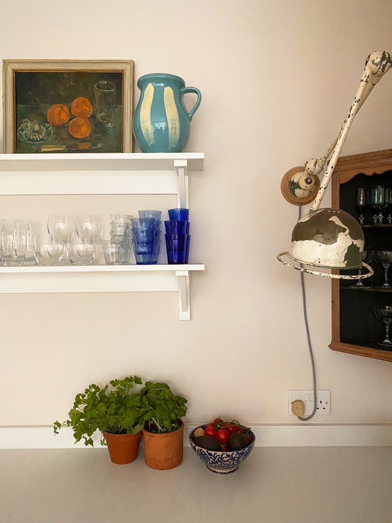 Vintage still life painting on open shelves with vintage wall light in kitchen of Natalie Williams, founder of Medium Room