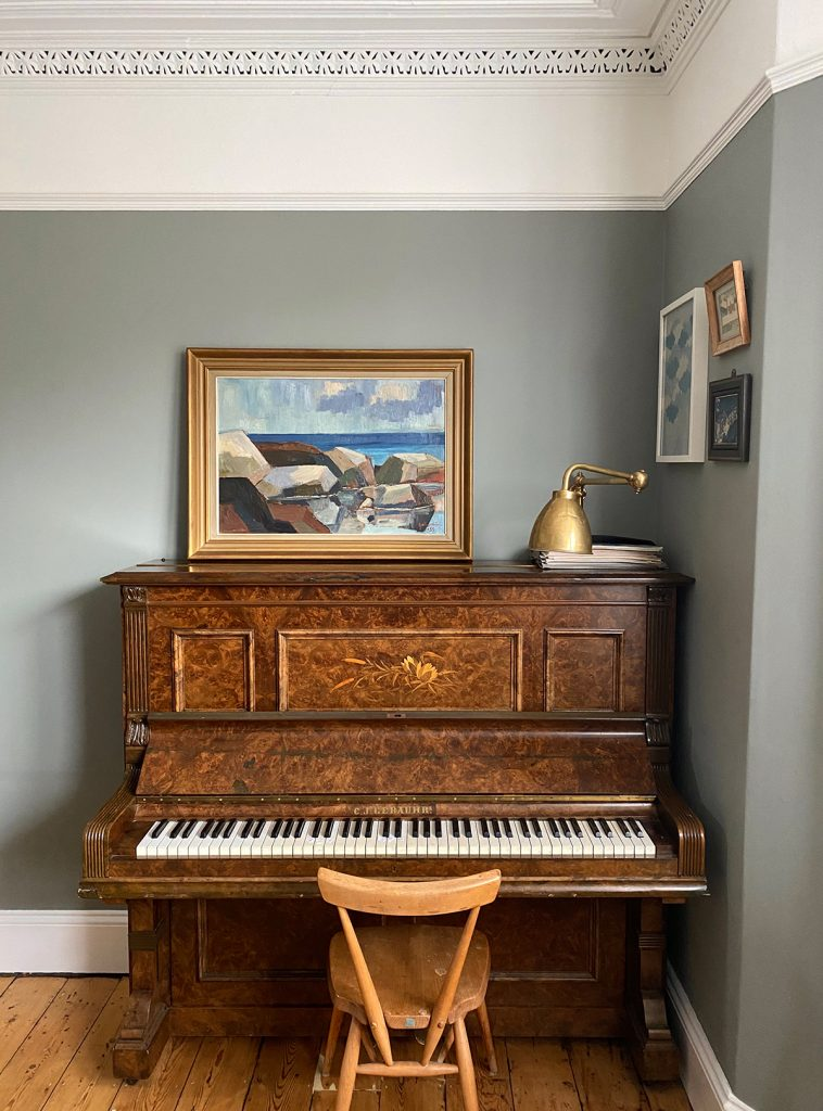 Piano with framed seascape painting and brass wall lamp with arm against grey wall and white cornicing, home of Natalie Williams, founder of Medium Room