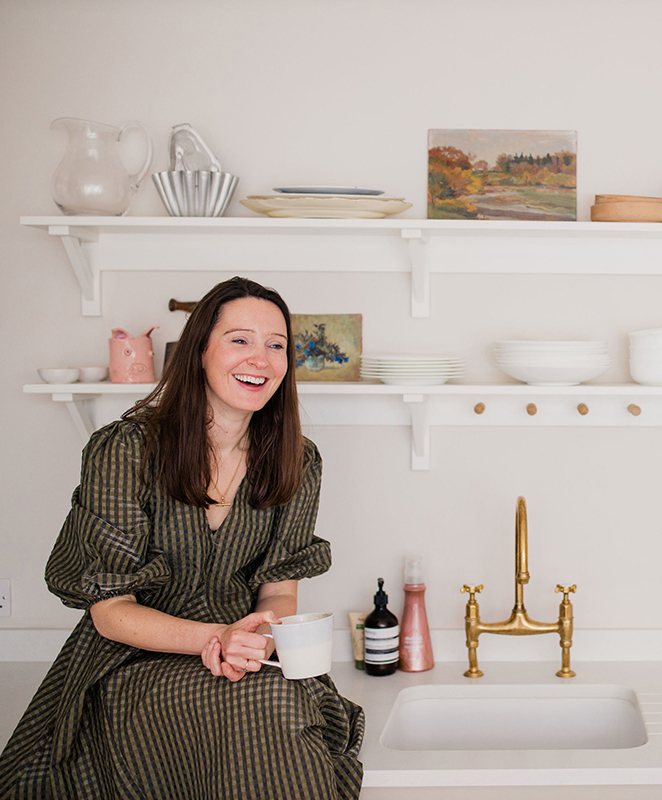 Natalie Williams founder of Medium Room vintage and antique art in white kitchen with open shelving, blue pitcher jug, still life vintage art and glassware