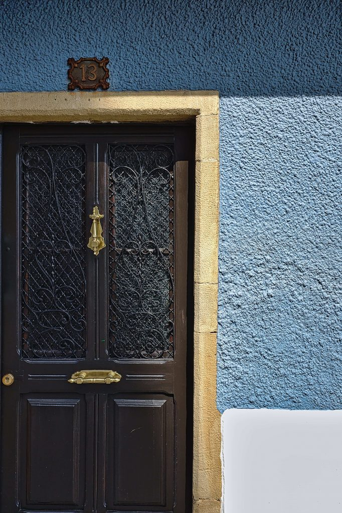 Front door with detailed ironwork and glass panels and brass doorknocker and letterbox. Photo-by-Eric-Prouzet / Unsplash