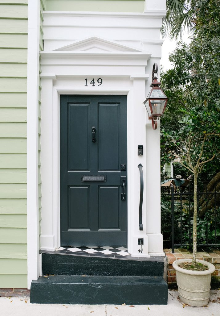 Dark green wooden from door with knocker and glassware lantern light and Ring doorbell. Photo-by-Kelsey-Schisler / Unsplash