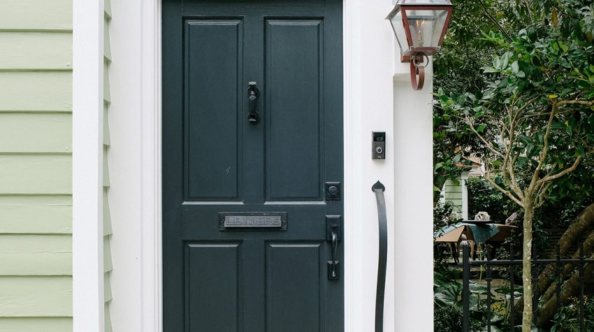 Dark green wooden from door with knocker and glassware lantern light and Ring doorbell. Photo-by-Kelsey-Schisler / Unsplash