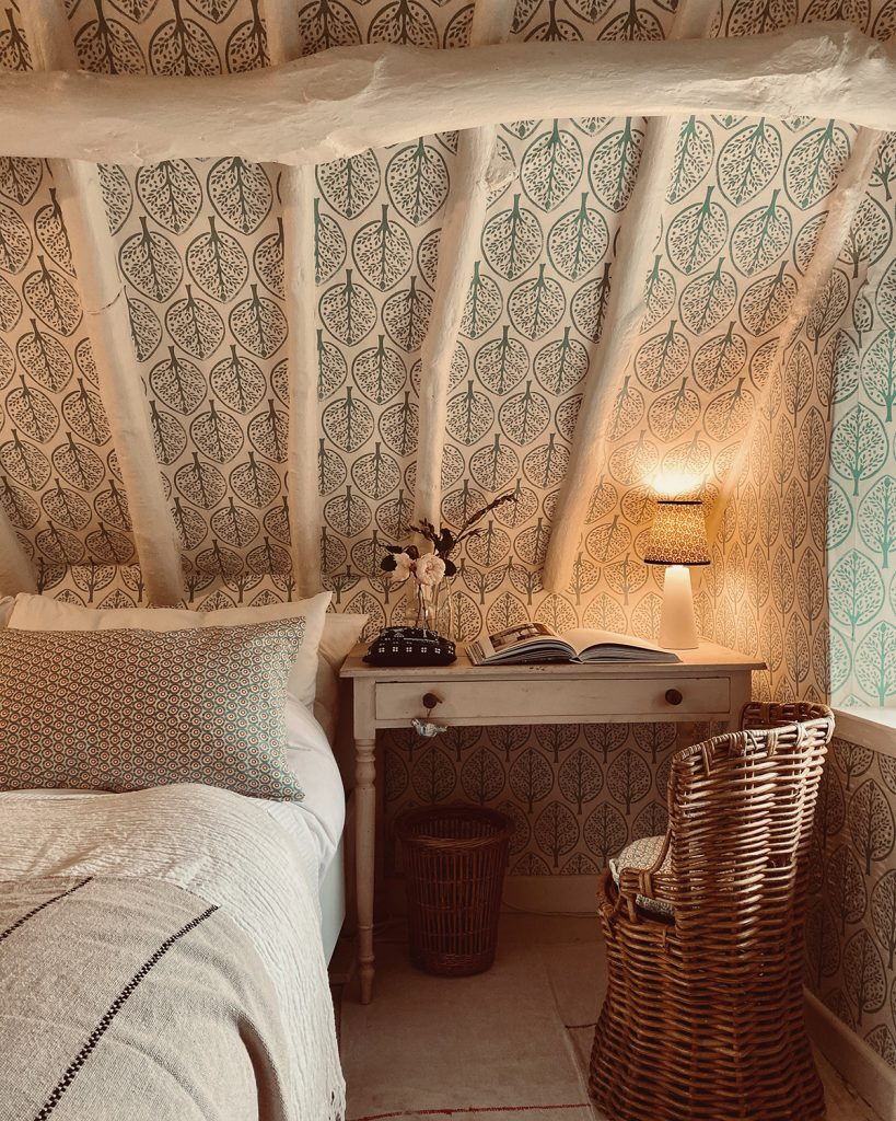 Molly Mahon leaf wallpaper, eaves, desk table and wicker chair in bedroom in the Cotswolds home of interior designer Victoria Barker, founder of Studio Faeger