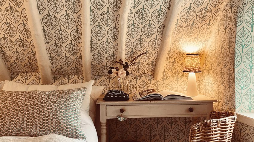 Molly Mahon leaf wallpaper, eaves, desk table and wicker chair in bedroom in the Cotswolds home of interior designer Victoria Barker, founder of Studio Faeger (Brightened)