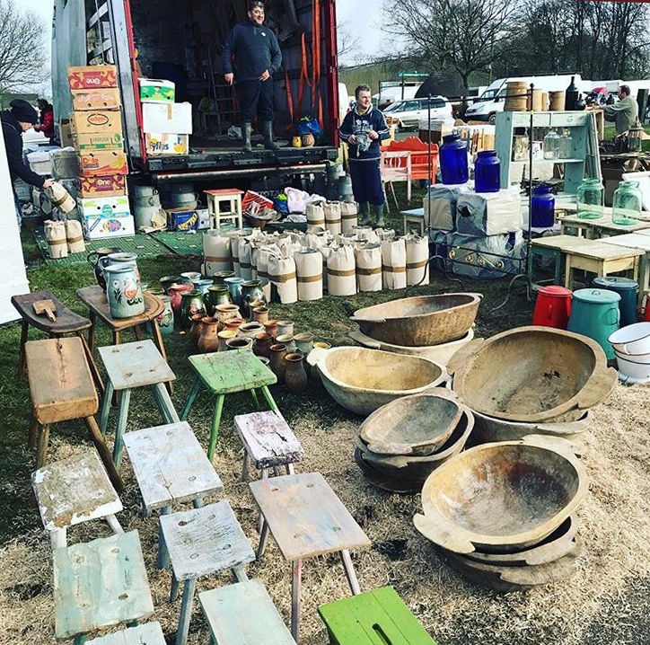 Sellers unloading a truck of glassware, wooden stools, wooden bowls, urns and vases at Ardingly Antiques Fair at South of England Showground