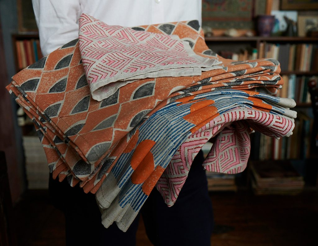 Molly Mahon holding pile of block printed fabric in the library at Charleston Farmhouse, home of the Bloomsbury Group in East Sussex