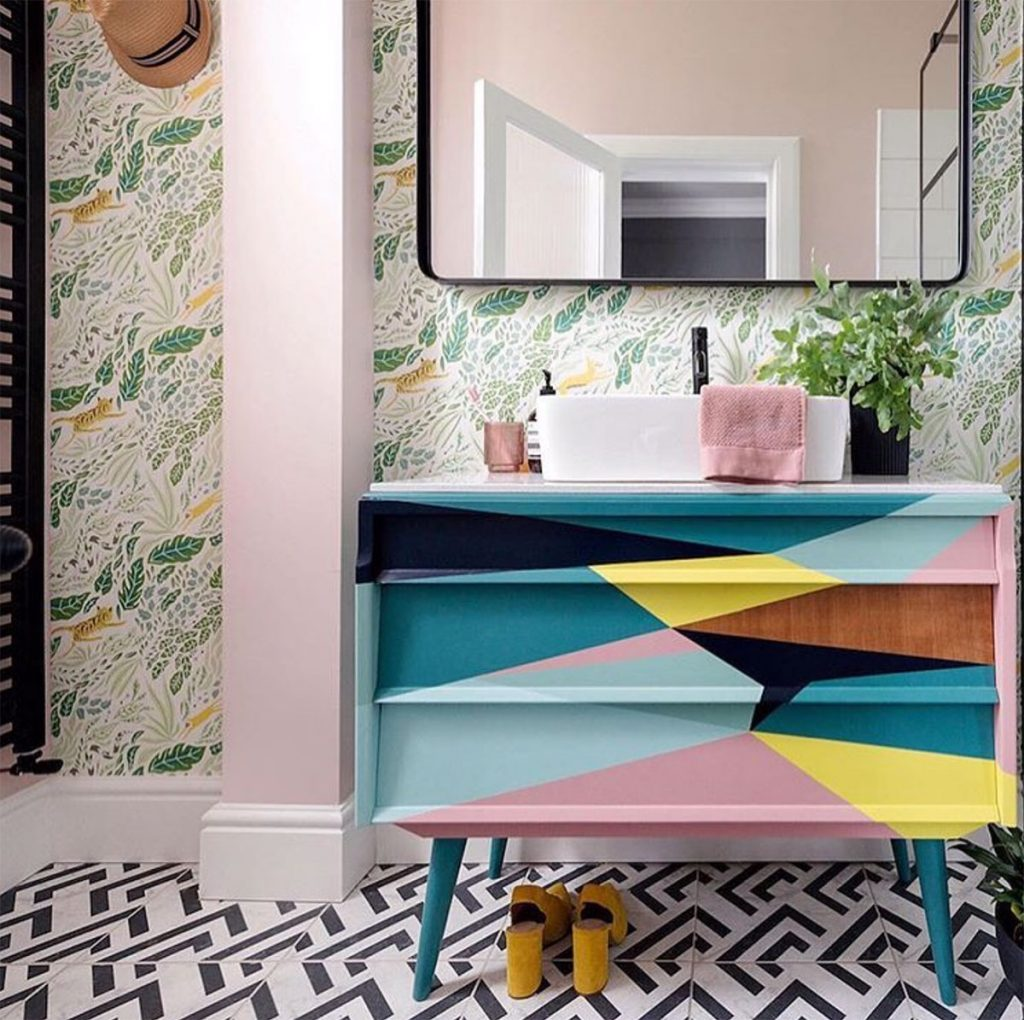 Bathroom with multicoloured vanity unit, leaf and animal wallpaper, monochrome graphic floor tiles by Liz Nylon