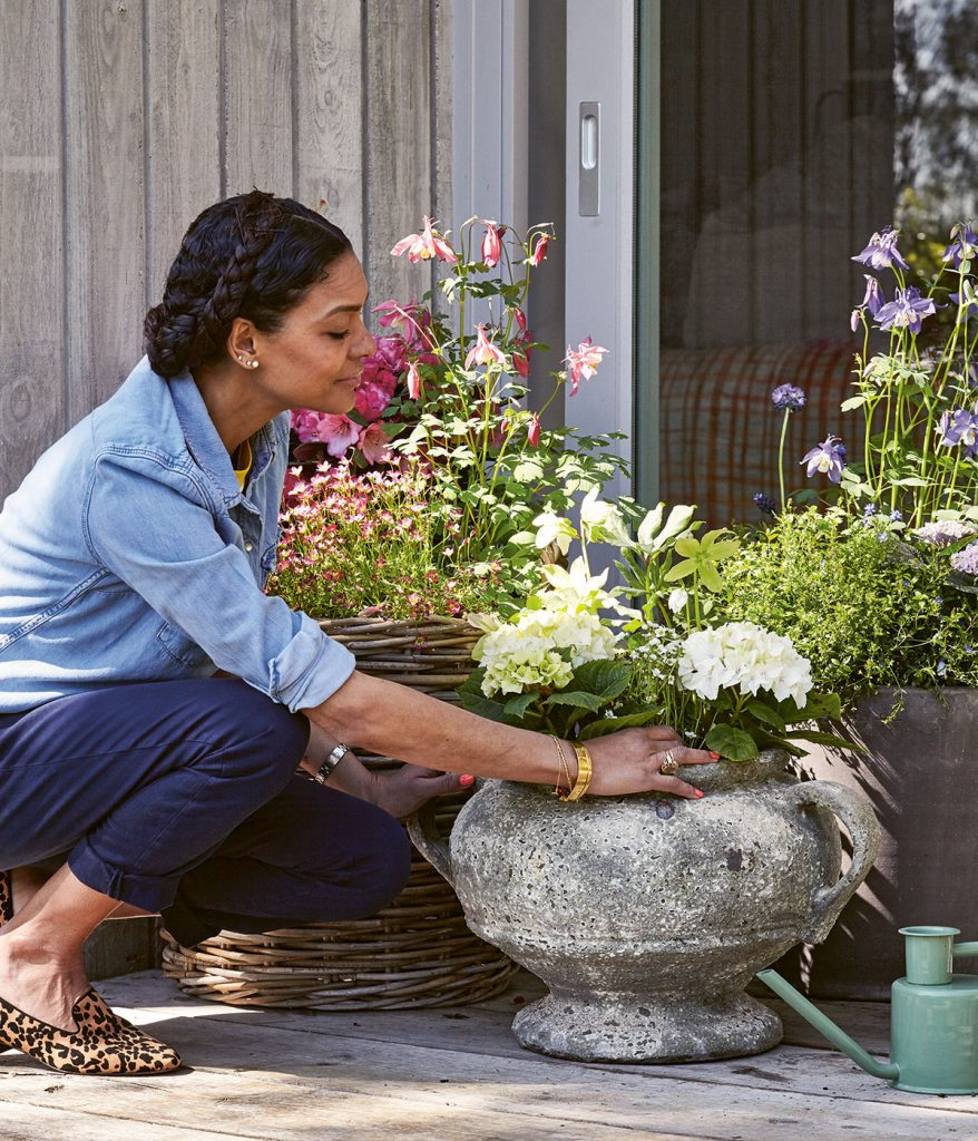 Gardenener Isabelle Palmer with wicker planter and stone urn filled with Rhododendron, Aquilegia, Hellebore, Hydrangea flowers from Modern Container Gardening book