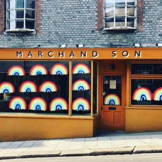Marchand Son shop front in Lewes, painted in golden yellow with rainbows painted on the windows