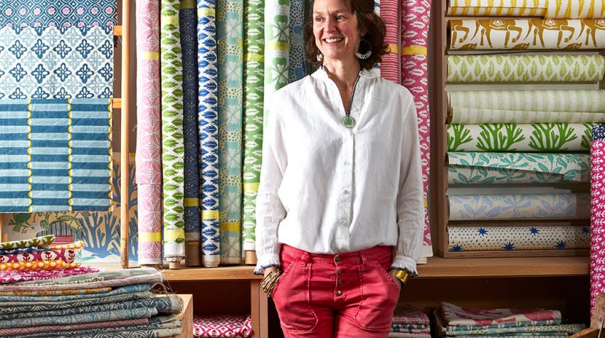 Molly Mahon standing in red jeans in front of her own designed block print fabrics. Photo by Sarah Hogan