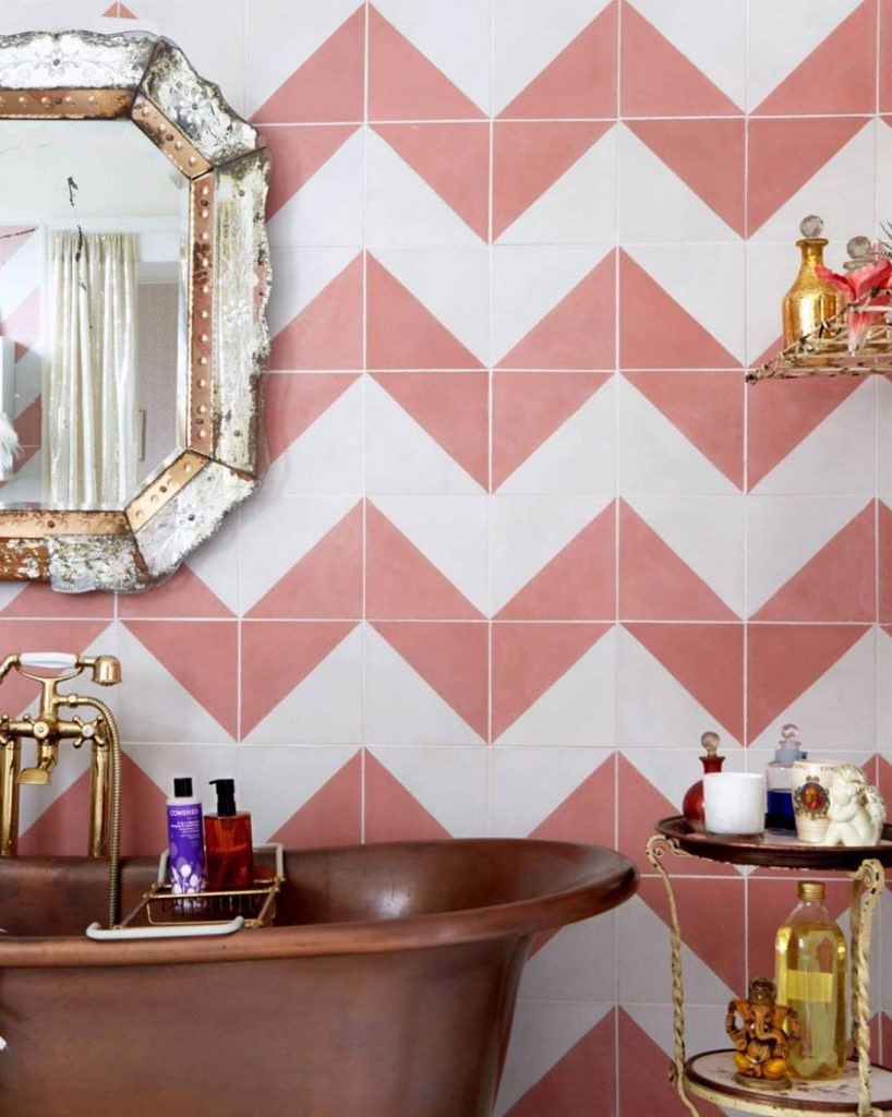 Pearl Lowe bathroom with pink and white chevron tiles by Bert & May, copper freestanding bath and glamorous glass mirror