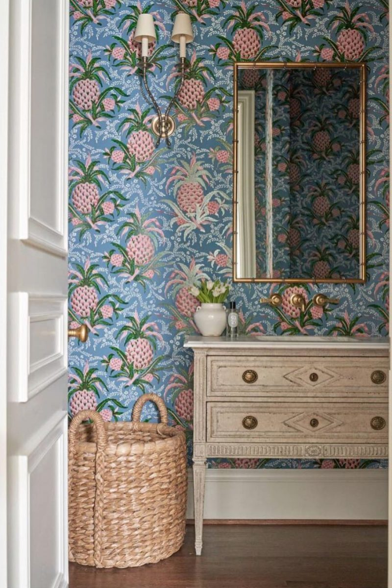 Bathroom with pineapple print wallpaper, carved wooden vanity unit, wicker basket, wall lights and wall-hung mirror designed by Amy Berry, photographer Nathan Schroeder
