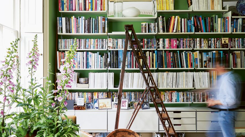 Shelves in a green sitting room belonging to Emilio Pimentel-Reid shelves Bold British Design ©Sarah Hogan
