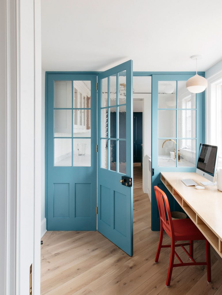 Desk area with red wooden chair and blue glazed internal doors, from Plain English at Long Island Beach House