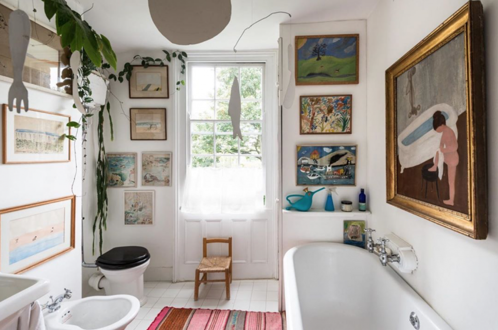 Bathroom of an artist with lots of original art on the walls and mobiles, Cannonbury Grove, London, marketed by The Modern House