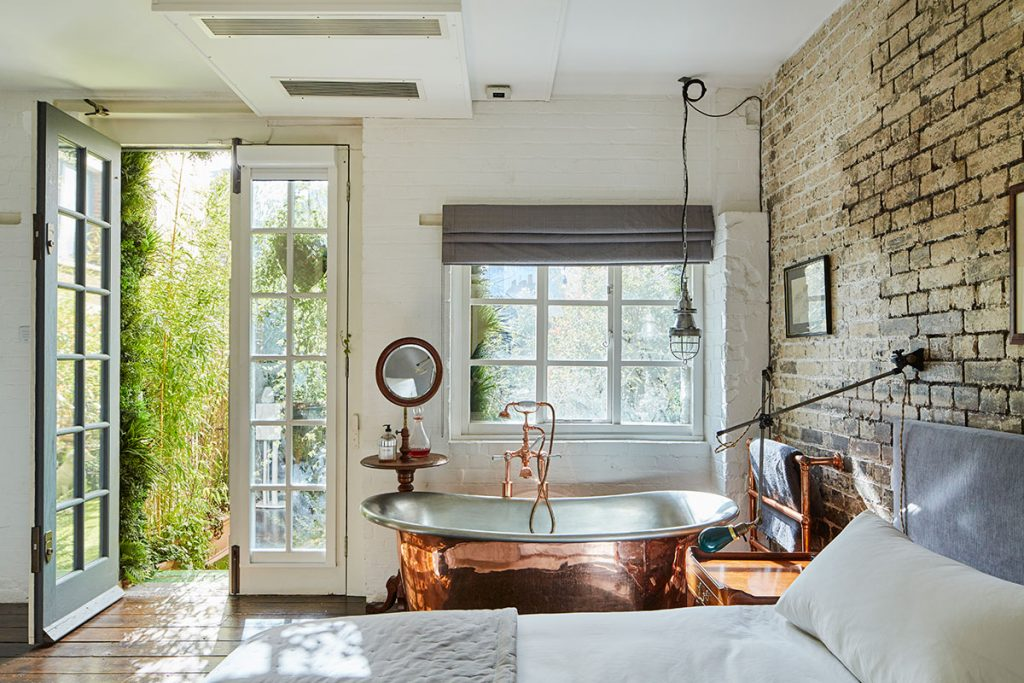 Copper freestanding bath and french doors from bedroom to garden at The Print House in Hoxton, London, for sale by The Modern House