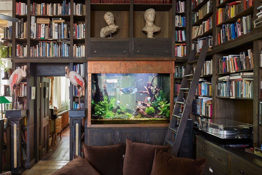 Fish tank, floor to ceiling book shelves and marble busts at The Print House in Hoxton for sale from The Modern House