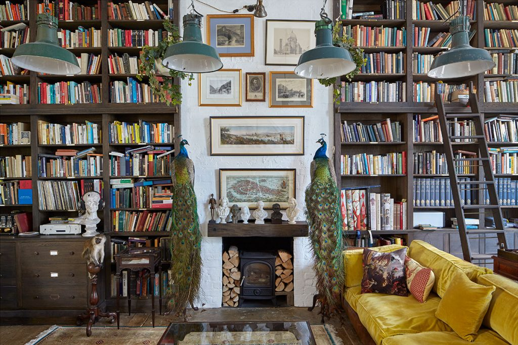 Log burner, mustard yellow velvet sofa, vintage pendant lights and floor to ceiling bookshelves at The Print House in Hoxton for sale with The Modern House