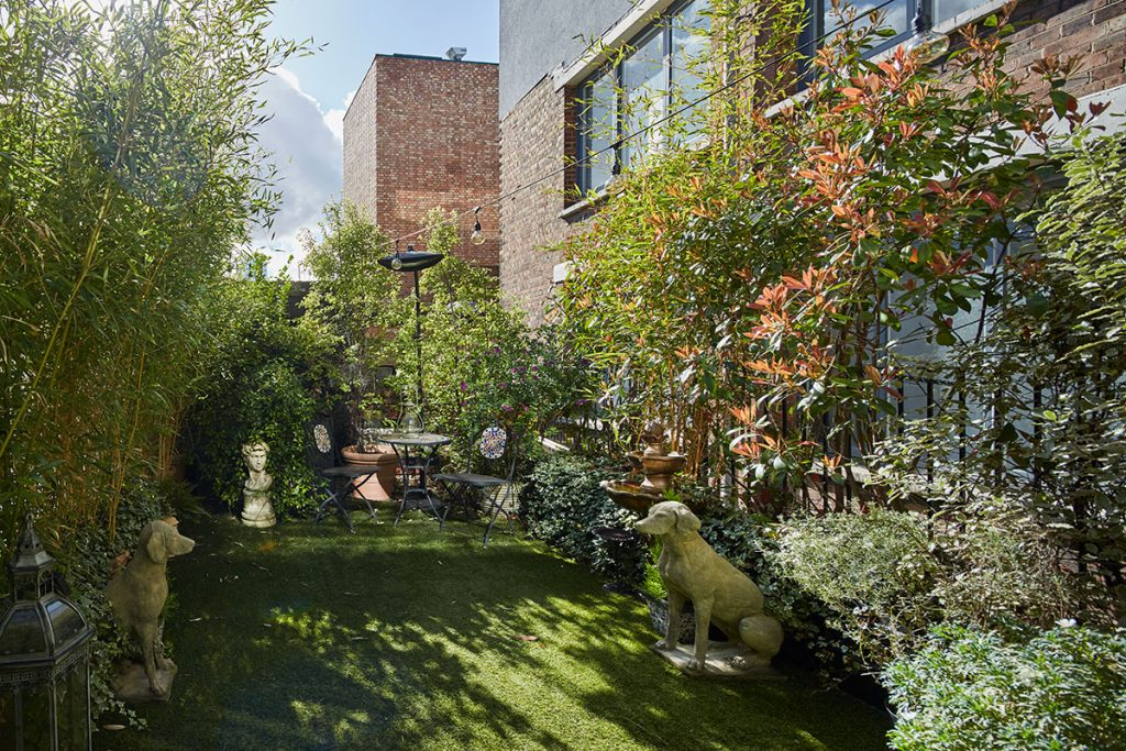 Green roof terrace with stone dogs at The Print House in Hoxton, London, for sale by The Modern House