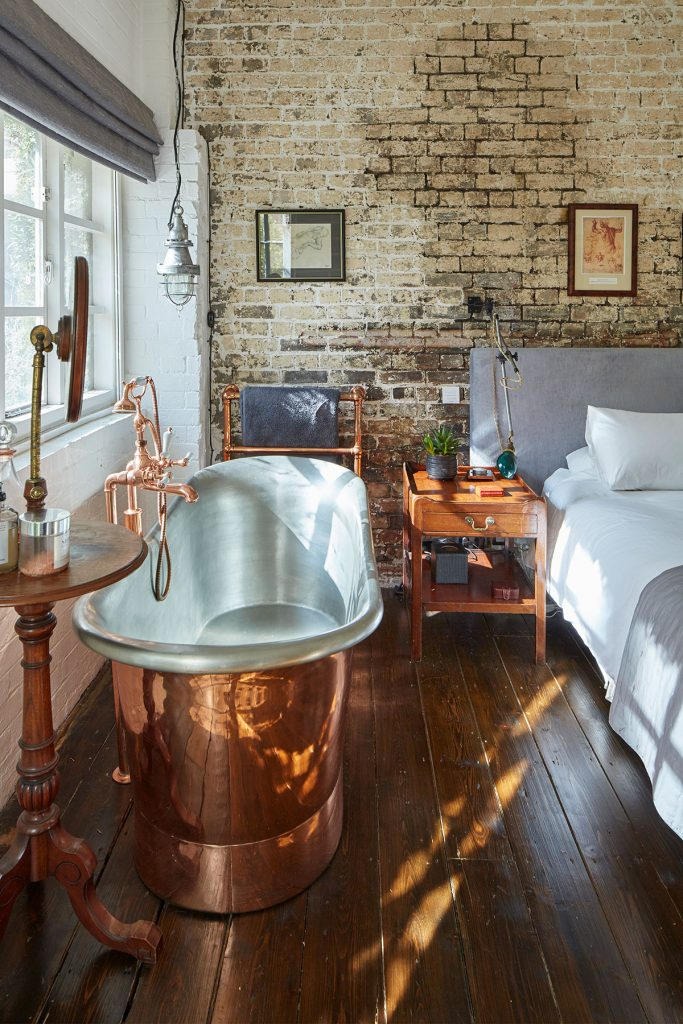 Copper freestanding bath and exposed brick wall in bedroom at The Print House in Hoxton, London, for sale by The Modern House