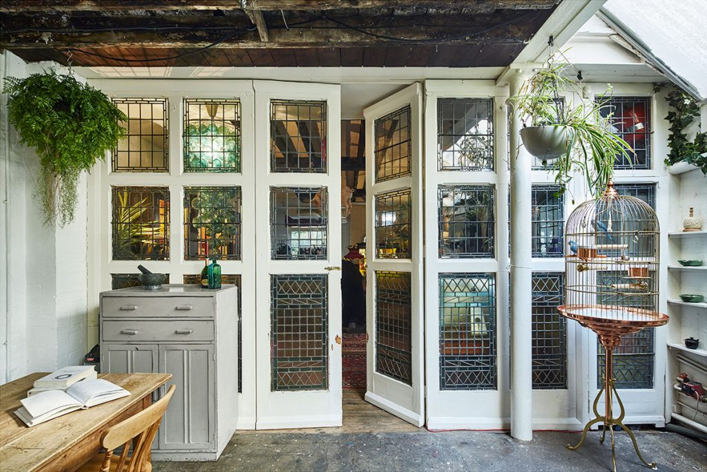 Stained Glass wood framed partition and doors with hanging plants at The Print House in Hoxton, London, for sale from The Modern House