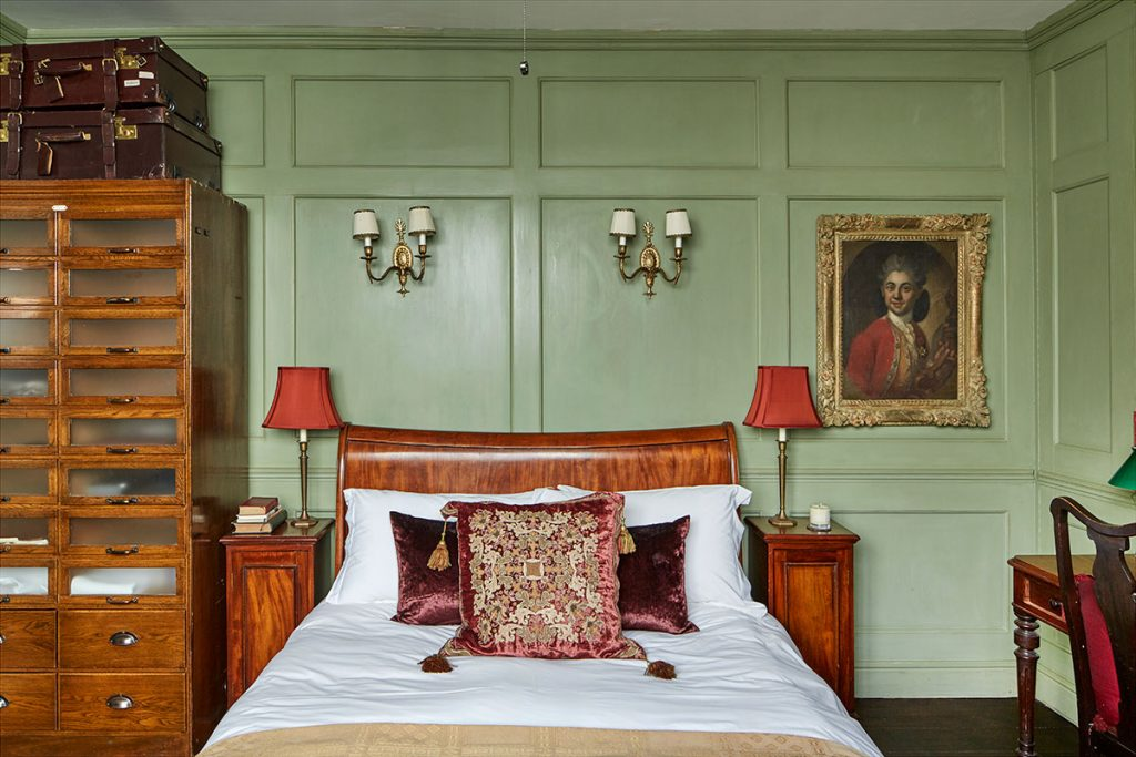 Roll top wooden bed and green panelled walls in bedroom at The Print House in Hoxton for sale from The Modern House