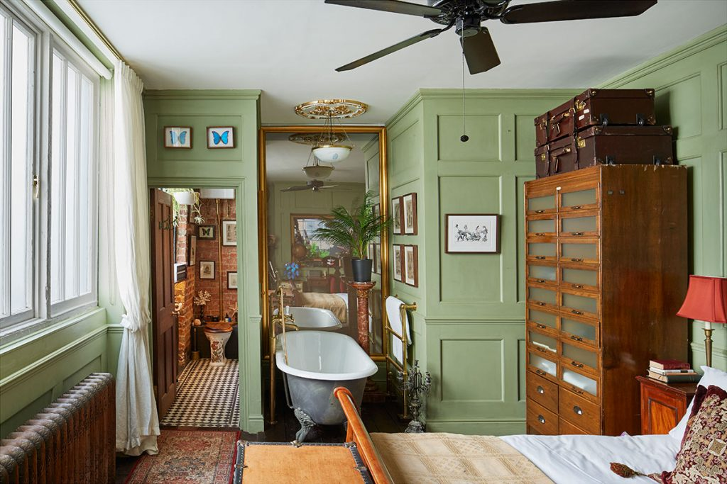 Green panelled bedroom with vintage chest of drawers and freestanding bath at The Print House in Hoxton for sale by The Modern House