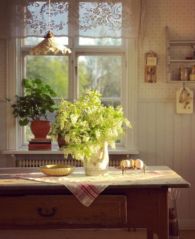 Lace curtain next to kitchen table with jug of flowers. Instagram/@underbaraclaras