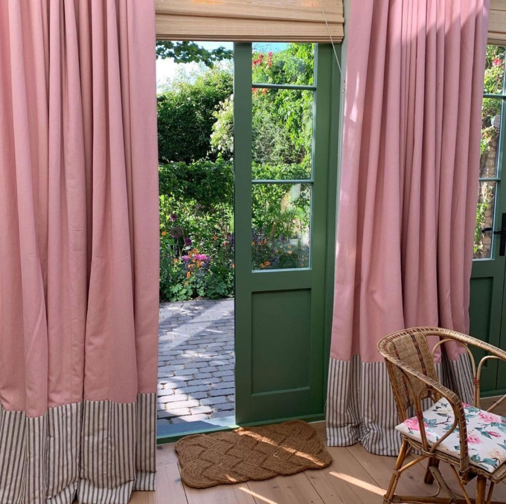Pink curtains with striped trim in Ian Mankin fabric at the home of Matilda Goad