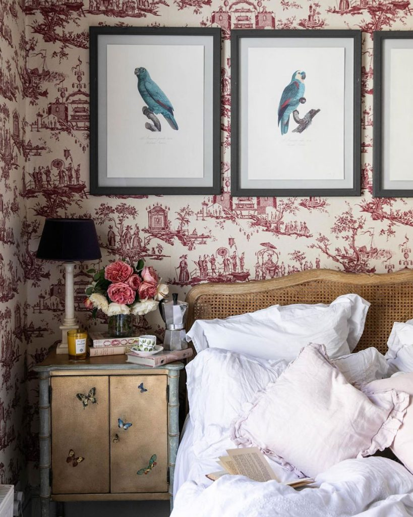 Cook and author Sky McAlpine's bedroom with cane headboard on bed, framed parrot pictures and bedside table with fresh flowers