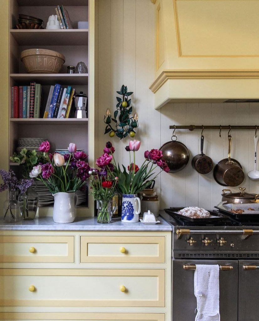 Cook and author Sky McAlpine's yellow kitchen with jugs or fresh flowers and range cooker