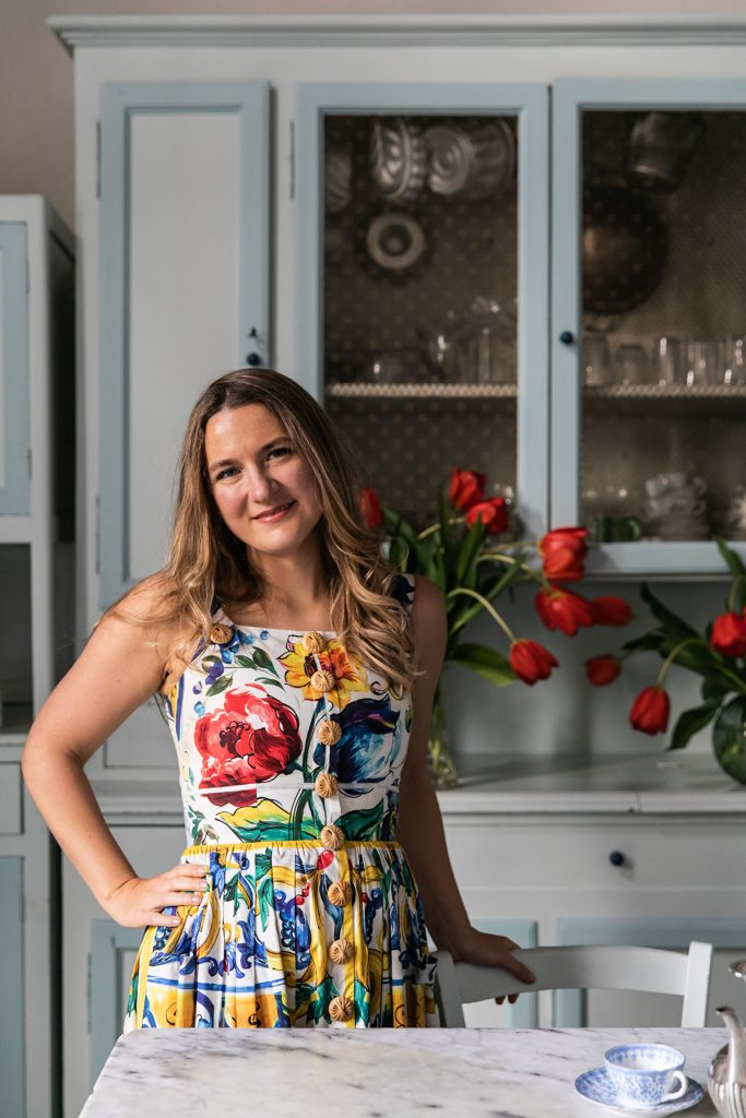 Cook and Writer Skye McAlpine wearing floral dress at home in her pale blue kitchen with red tulips