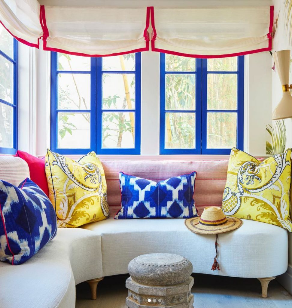 Banquet seating with colourful cushion, blue framed windows and white blinds with red trim. Instagram @ellenkavanaugh