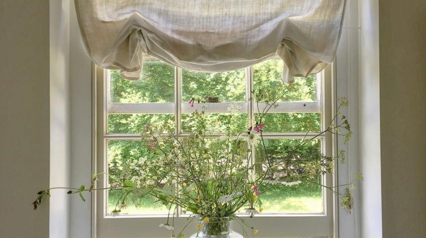 Pretty little window with natural linen blind and vase of flowers. Instagram @marialemesurier