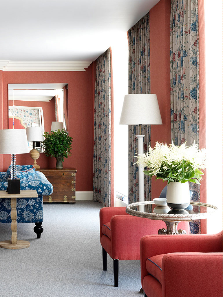 Deep salmon pink walls, red upholstered chairs and full length curtains in Crosby-Street-Hotel-suite, New York, Firmdale Hotels designed by Kit Kemp