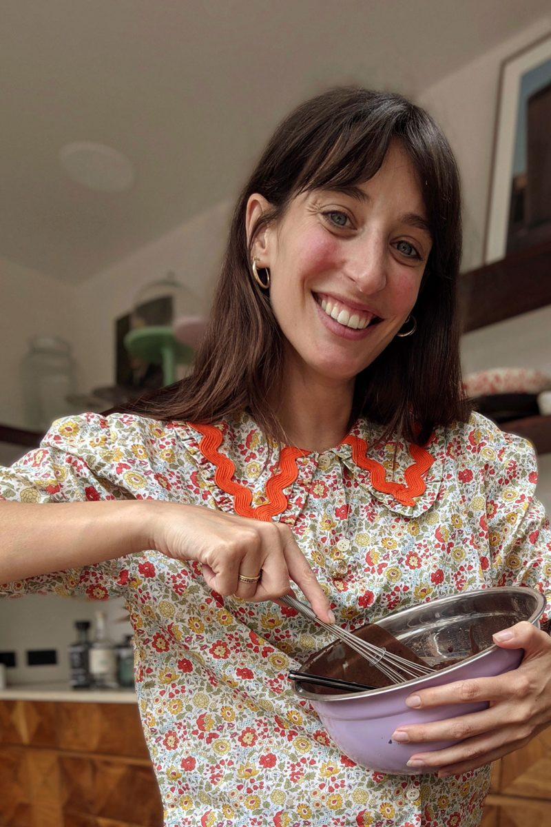 Laura Jackson wearing floral top with bold collar holding mixing bowl