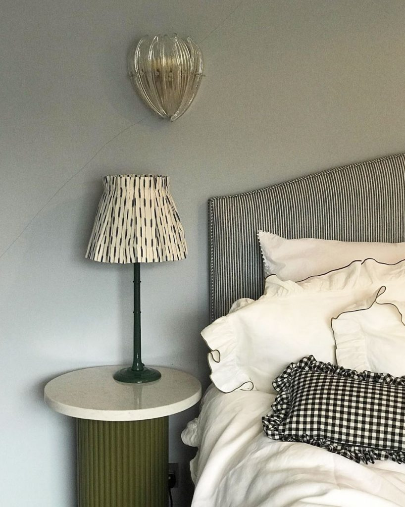 Monochrome bedroom with olive green bedside table at the London home of Laura Jackson