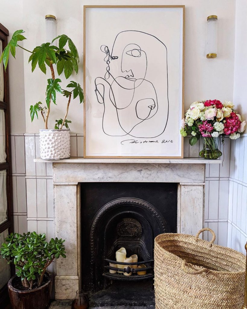 Framed line drawing above marble fireplace with fresh flowers, plants, wicker basket and wall lights in the bathroom of Laura Jackson