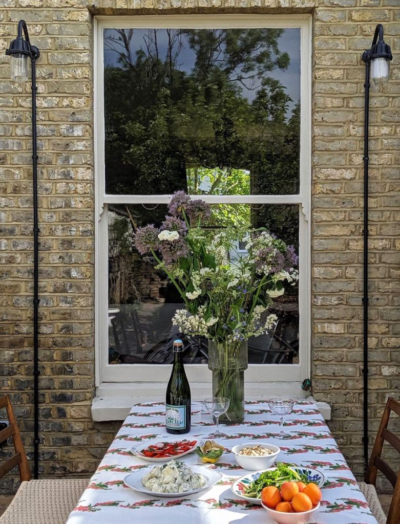vase of flowers and table paid with tablecloth in the bag yard of the London home of Laura Jackson