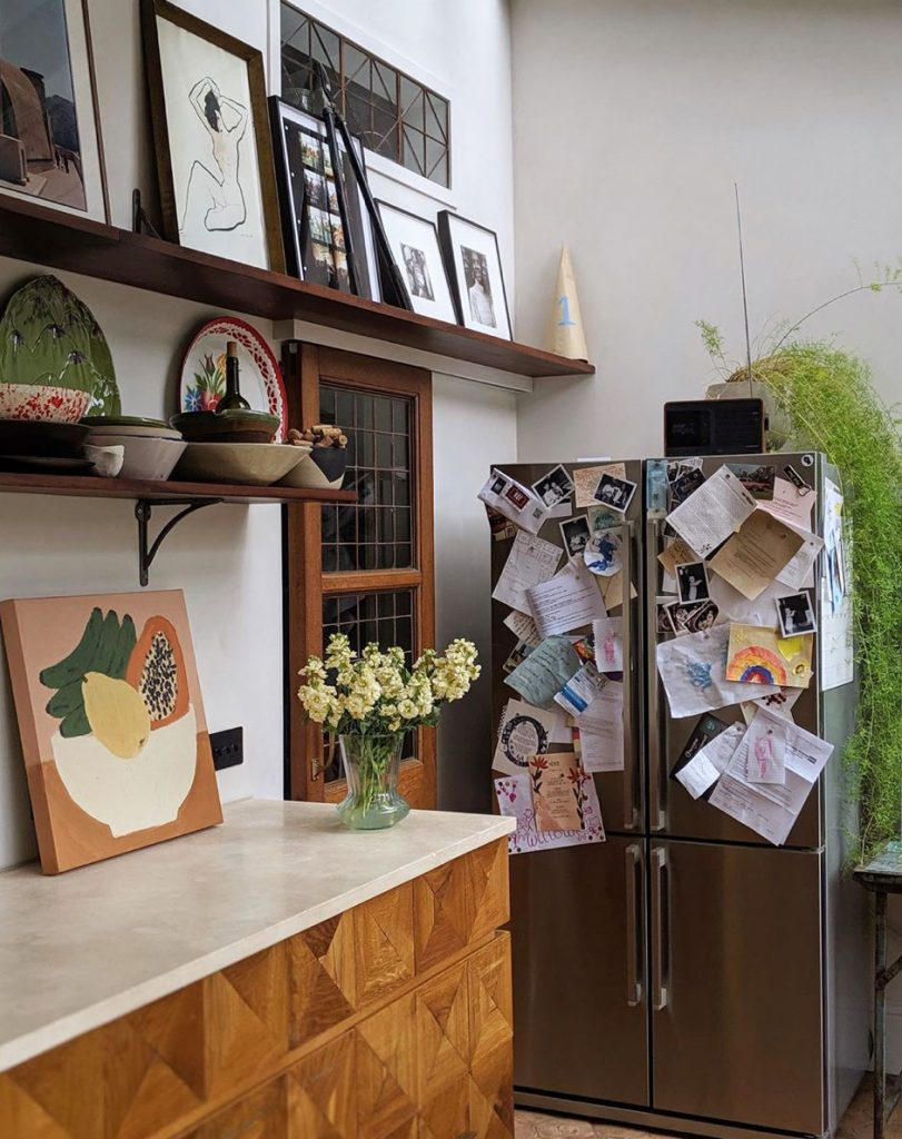 Fridge covered in photographs and pictures, open shelving and art in the kitchen of Laura Jackson