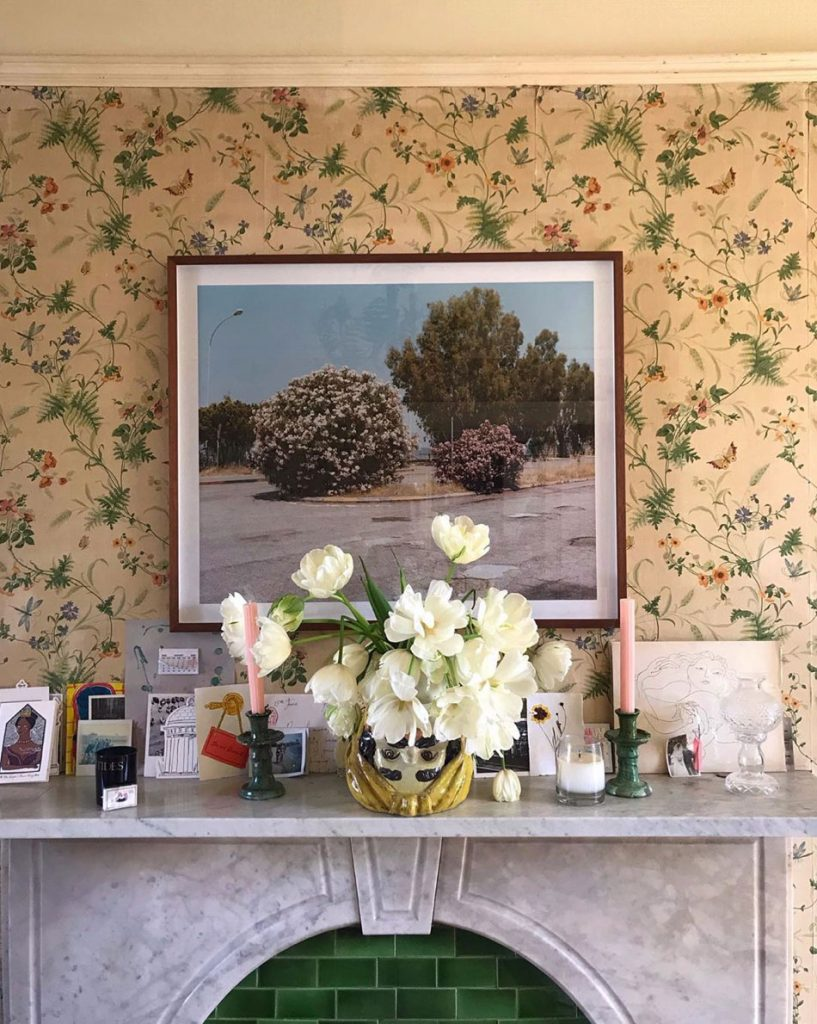 Marble fireplace, floral wallpaper, framed photograph, vase of white tulips, candlesticks and cards in the London home of Laura Jackson