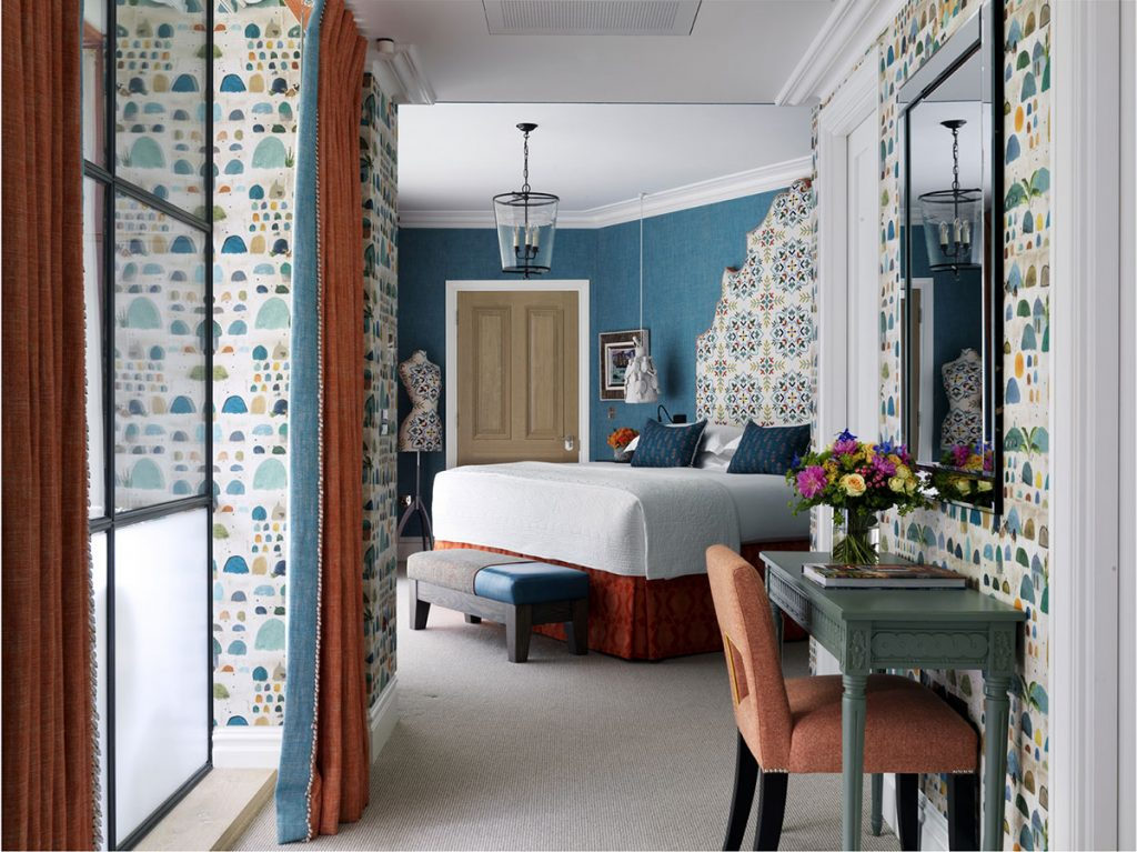 Console table, bold patterned wallpaper, curtain detail and oversized headboard in the Oak-leaf-suite-Ham-Yard-hotel-Firmdale Hotels designed by Kit Kemp