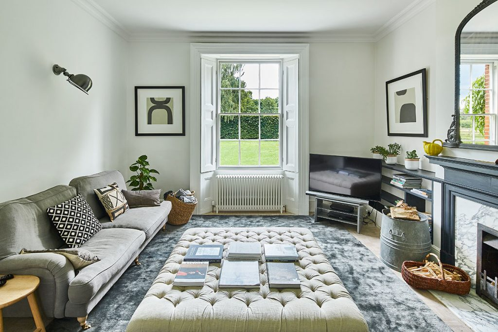White walls, grey furnishings and white window shutters in the television room at the home of Simone-Bunting in Pangbourne, Berkshire. Credit: The-Modern-House