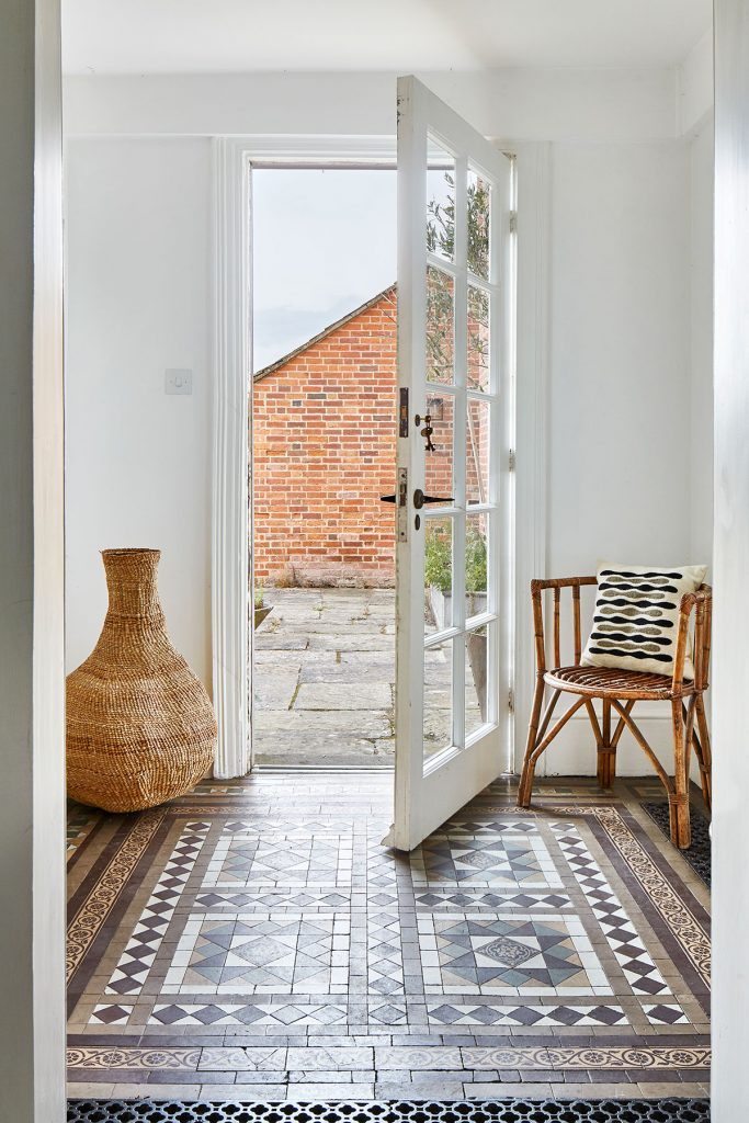 Wicker basket, cane chair and marron ceramic floor tiles at the home of Simone-Bunting in Pangbourne, Berkshire. Credit: The-Modern-House