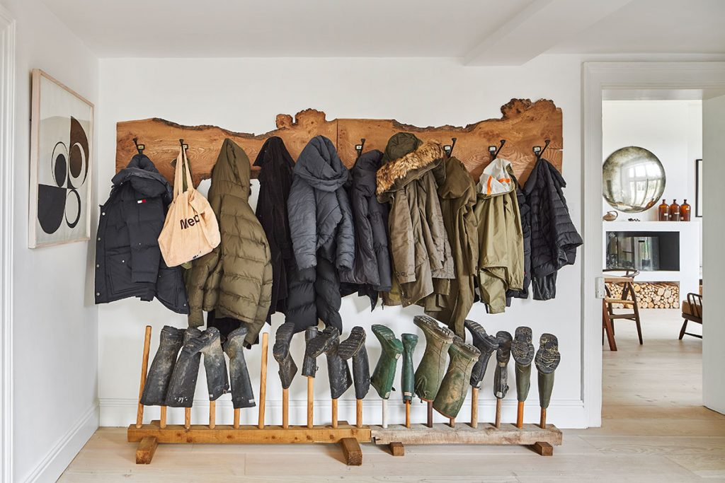 Wooden coat rack and wellie boot rack and modern art in the entrance hall at the home of Simone-Bunting in Pangbourne, Berkshire. Credit: The-Modern-House
